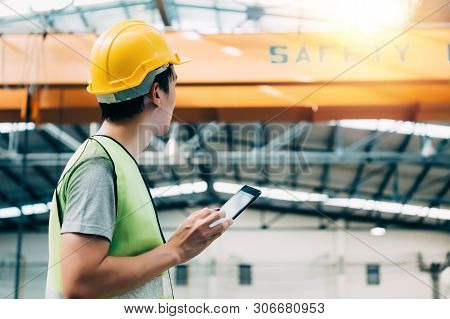Young Asian Male Heavy Industral Worker Using A Digital Tablet Inside Manufacturing And Factory Site