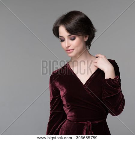 Beauty female portrait. Young attractive woman posing at studio over gray background. Beautiful model with perfect make-up dressed evening burgundy dress looking down