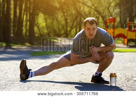Close Up Healthy Caucasian Athlete Stretching Legs Looking Ahead. Handsome Man With Bottle Of Water