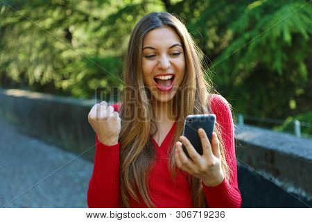 Exuberant Young Woman Cheering At Good News On Her Mobile Phone And Punching The Air With Her Fist