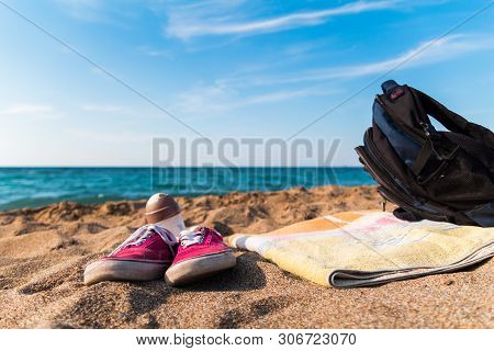 Red Shoes Towel Backpack On The Sandy Beach Sea As Background. Quick Dive. Beach Escape. Quick Dive.