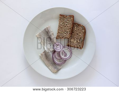 Fresh Pickled Herring On A Plate With Homebaked Rustic Seeded Rye Bread And Onion Rings. Scandinavia