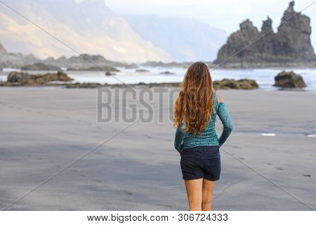 Back view of girl walking reflexive e tranquil on hidden amazing beach on sunrise. Young female discovering wild paradisiac black beach in Tenerife Island. poster