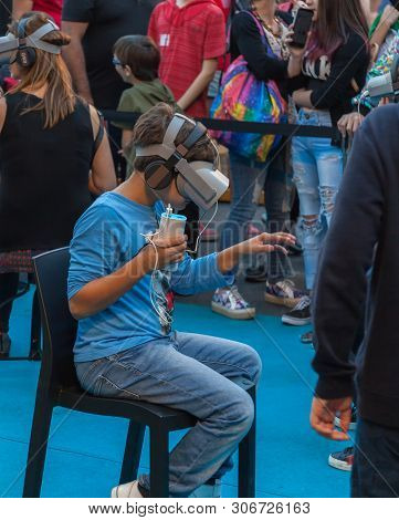 A Boy And Girl Explore The Possibilities Of Virtual Reality Glasses At A Street Exhibition, On Sante