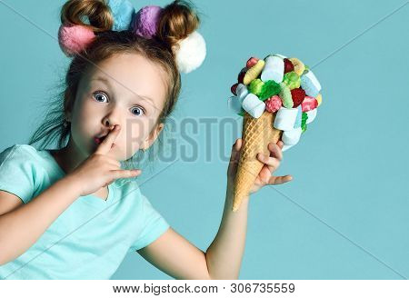 Closeup Portrait Of Happy Little Girl Kid Holding Big Ice-cream In Waffles Cone With Tasty Toppings