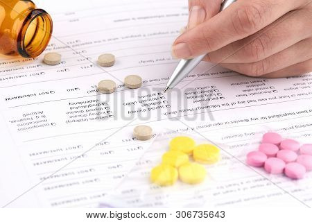 Colorful Pills, Brown Vial And Hand Writing On Medical Questionnaire Form.