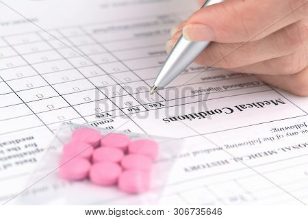 Pink Pills And Hand Writing On Medical Questionnaire Form.