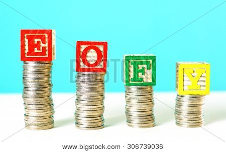End Of Financial Year And Savings Concept Stacking Coins With Building Blocks.