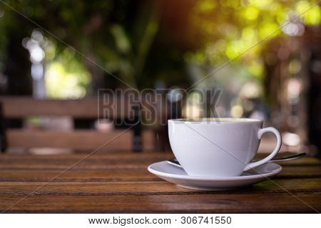 Wood Table With Cup Of Latte Coffee In Morning Garden, Side View.