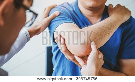 Physical Doctor Consulting With Patient About Elbow Muscule Pain Problems Physical Therapy Diagnosin