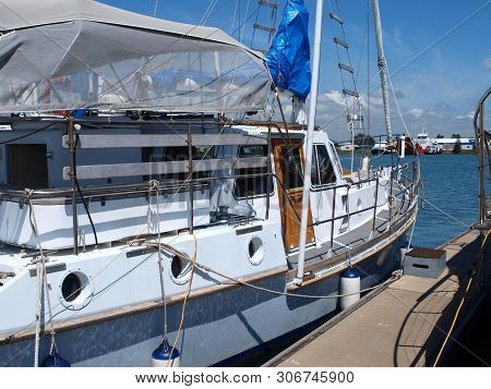 Gladstone Marina. Sailboat Tied Up To A Marina Floating Walkway In Tropical Water With Blue Sky Back