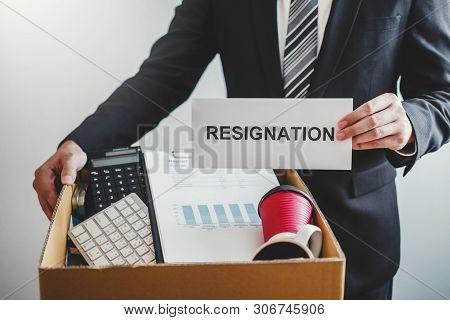 Business man stressing with resignation letter for quit a job packing the box and leaving the office , Resignation concept poster