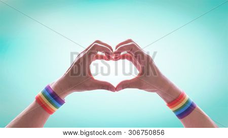 Lgbt Pride Month With Rainbow Flag Ribbon Wristband On Lgbtq People Heart-shape Hands For Internatio