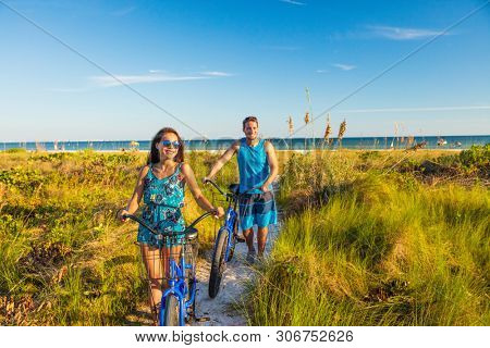 Summer people lifestyle happy couple biking on beach relaxing outdoors activity at sunset. Young woman and man riding recreational bikes bicycles on USA Florida holidays getaway.