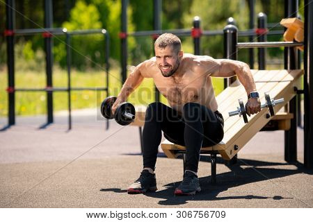 Young muscular shirtless athlete sweating while doing difficult exercise for muscles on sportsground