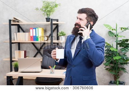 Coffee is pledge of successful negotiations. Caffeine addicted. Man bearded businessman hold cup and smartphone. Mobile call. Start day with coffee. Coffee relaxing break. Boss enjoying energy drink. poster