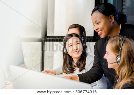 Friendly black businesswoman supervisor training work to her multiethnic colleagues in call center office poster