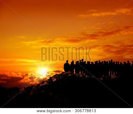 group of silhoutted people on hill watching view over orange colored sunset sky
