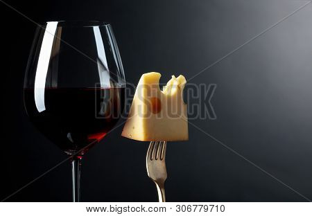Maasdam Cheese With Red Wine On A Black Background. Copy Space.