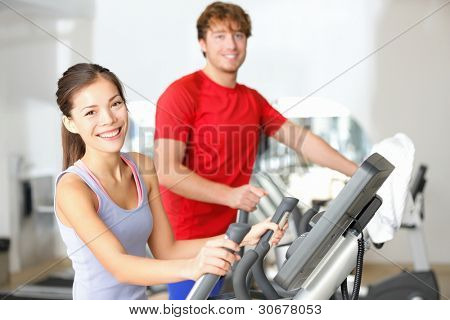 Fitness center people smiling happy working out on moonwalker fitness machines in fitness center. Asian woman, Caucasian man.