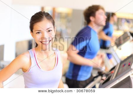 Fitness people portrait in gym. Woman smiling happy during running workout on treadmill in fitness center. Mixed race Cauasian / Chinese Asian female fitness model.
