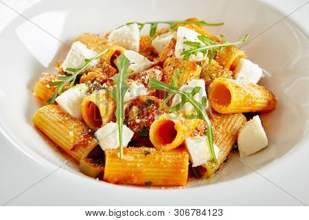 Exquisite Serving White Restaurant Plate of Homemade Rigatoni in Tomato Sauce with Milk Mozzarella. Stylish High Kitchen Italian Penne Pasta Tubes on Natural Black Marble Background