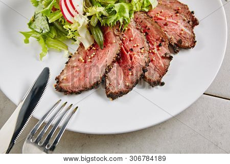 Roast Beef Salad with Green Mix. Thick Slices of Juicy Medium Rare Veal or Grilled Steak on White Plate with Sliced Radish, Tomatoes, Spices and Green Lettuce