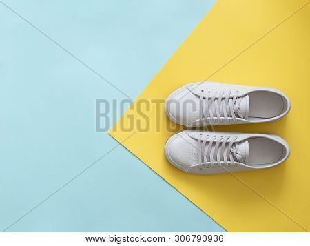 White Leather Sneakers On Blue And Yellow Background. Pair Of Fashion Trendy White Sport Shoes Or Sn