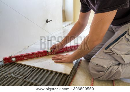 Young Worker Tiler Installing Ceramic Tiles Using Lever On Cement Floor With Heating Red Electrical