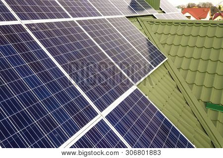 Close-up surface of blue shiny solar photo voltaic panels system on building roof. Renewable ecological green energy production concept. poster