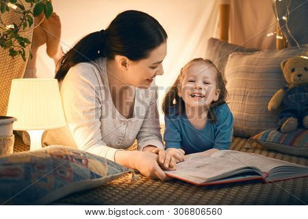 Family bedtime. Mom and child daughter are reading a book in tent. Pretty young mother and lovely girl having fun in children room.
