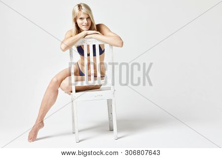 Frontal View Of A Girl In Bikini Sitting Over A White Chair Isolated In Studio With A White Backgrou