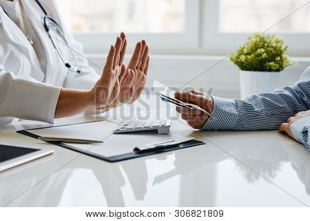 A Female Doctor Refuses A Bribe From Her Patient In Medical Office