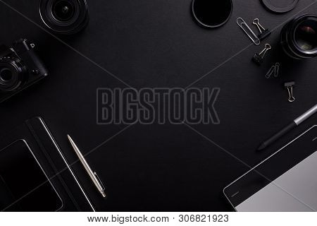 Top View Of The Black Table Graphic Designer With Camera, Lenses And Diary With Copy Space