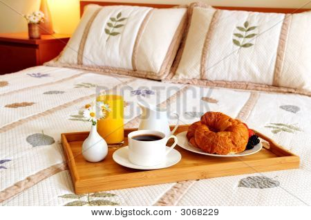 Tray with breakfast on a bed in a hotel room poster