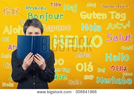 Student Woman Holding A Textbook Over Yellow Wall Written With Word Hello Translated In Different La