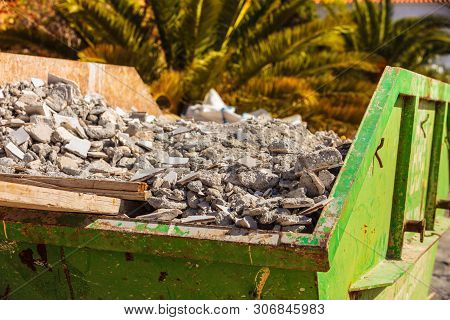 Green Metal Container With Construction Waste Rubble For Disposal. Heavy Garbage On Construction Sit