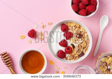 Greek Yogurt In Bowl With Raspberries, Honey And Muesli On Pink Table Top View. Healthy Diet Breakfa