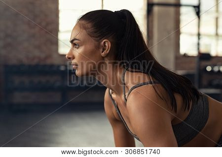 Young woman doing squat exercise while looking away at gym. Closeup of muscular girl while exercising in fitness center. Fit and concentrated woman doing strength workout.