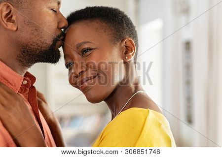 Romantic mature man kissing woman on forehead. Loving couple enjoying spending time together. Closeup face of beautiful wife receives a sweet kiss from husband on forehead for their anniversary.