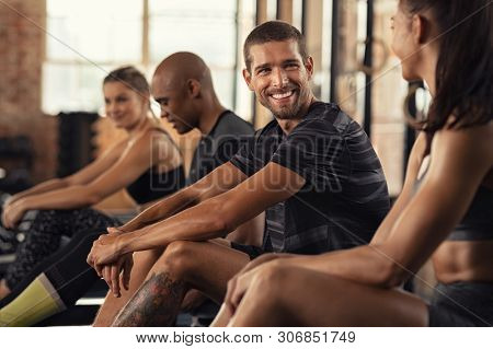 Portrait of cheerful young man sitting at rowing machine and talking with woman at gym. Smiling sportsman relaxing after workout with his friends at gym. Smiling guy and girl having conversation.
