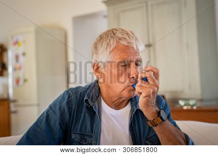 Senior man using asthma inhaler for relief an attack at home for preventing attack. Old man using medical inhaler to prevent and treat wheezing and shortness of breath caused by allergy.