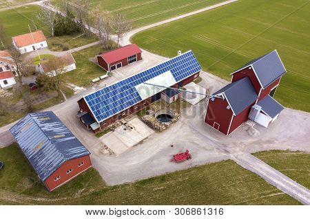 Top View Of Rural Landscape On Sunny Spring Day. Farm With Solar Photo Voltaic Panels System On Wood