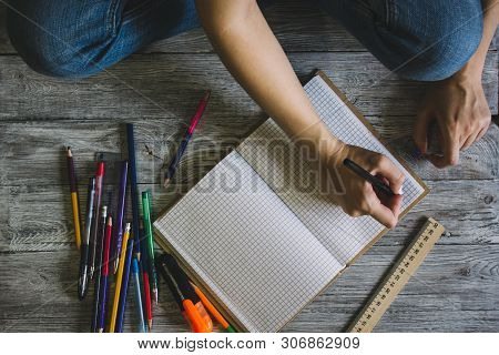 Right-handed Woman Holding Pen While Writing On Small Notebook On Wooden Rusty Floor