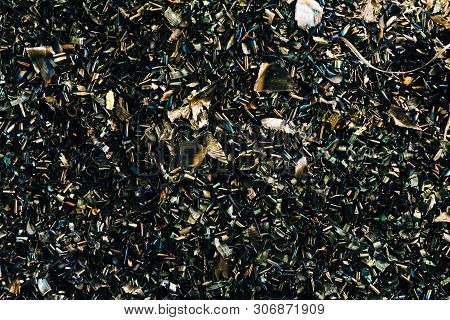 Metal shavings background. Short dark colored steel shavings after temperature exposure from a cutting tool. poster