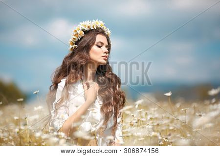 Beautiful young girl with flower enjoying in chamomile field. Carefree happy brunette woman with chaplet on healthy wavy hair having fun outdoor in nature. People freedom style. poster