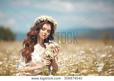 Beautiful young girl with flowers enjoying in chamomile field. Carefree happy brunette woman with chaplet on healthy wavy hair having fun outdoor in nature. People freedom style. poster