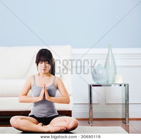 Asian woman sitting on a yoga mat doing the salutation seal pose. Meditation.