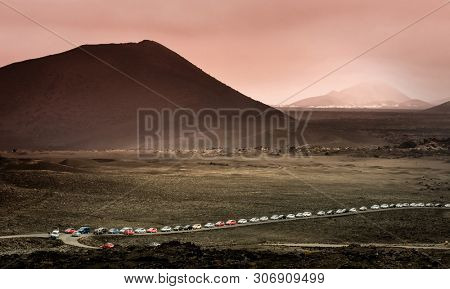 beautiful mountain landscape with a queue of cars in Timanfaya National Park in Lanzarote, Canary Islands