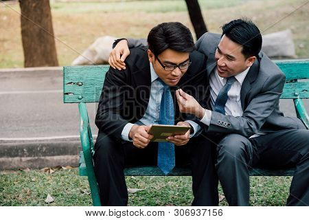 Gay Couple Businessman Sitting In The Garden After Work.teamwork Friendship Business People Greeting